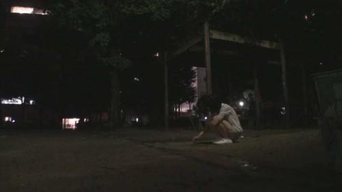 夜の公園で1人で遊ぶ白い服を着た女の子