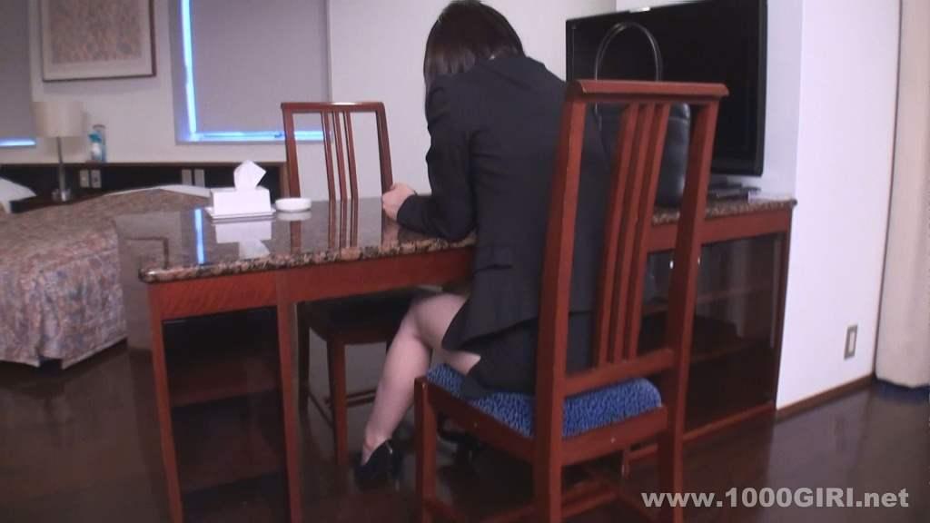 椅子に座ってテーブルでスマートフォンを操作するスーツ姿のOL